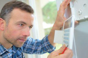 Adult man analyzing alarm keypad in home.