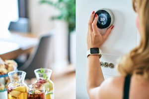 a woman adjust the temperature in her energy efficient home before guests arrive