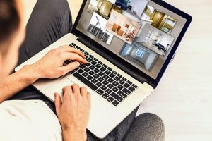 Home buyer looks for a home online on his laptop by comparing modalities in the pictures taken of each property.